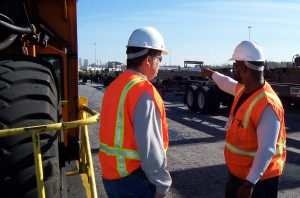 Two men wearing hard hats and reflective vests talking